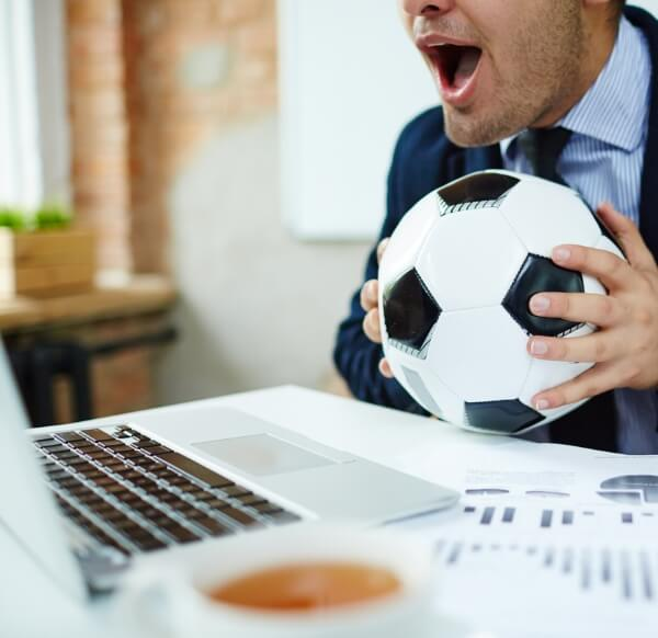 Businessman with football / istock - shironosov