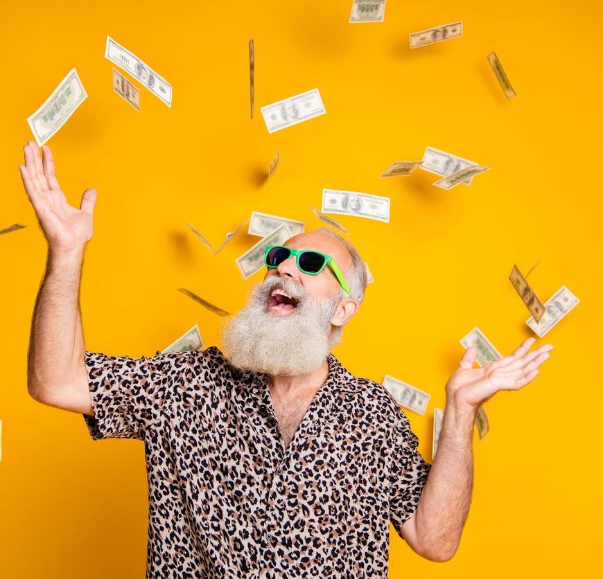 Funky old man enjoying a money rain (istock/deagreez)